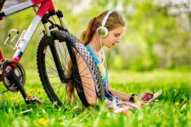 flicka med hörlurar och bok sitter lutat mot cykel på grönt gräs