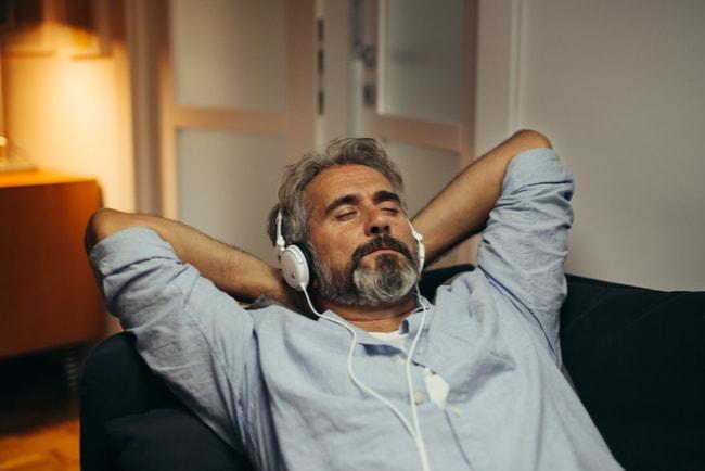 Medelåldersman ligger i soffan med hörlurar.