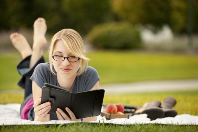 kvinna ligger på en duk i en park och läser e-bok
