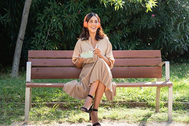 Kvinna sitter på parkbänk och lyssnar på ljudbok.