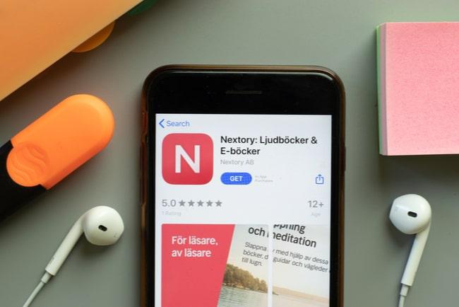 mobil med nextory-appen uppe ligger på bord med hörlurar runt sig