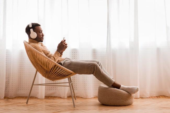 man sitter i stol och lyssnar på ljudbok