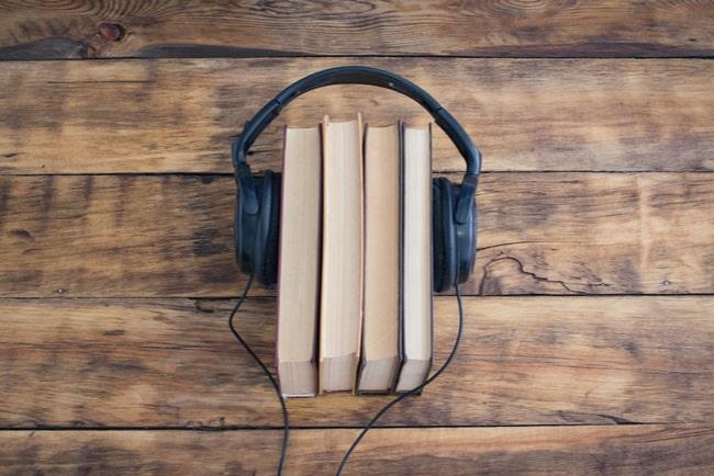 hörlurar runt fyra böcker som ligger på träbord