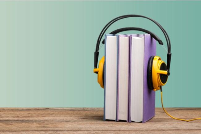 hörlurar runt tre böcker