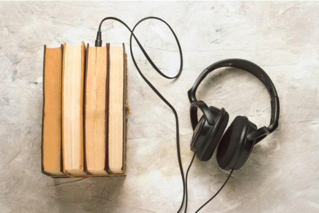 hörlurar med sladd som går till böcker, koncept ljudböcker