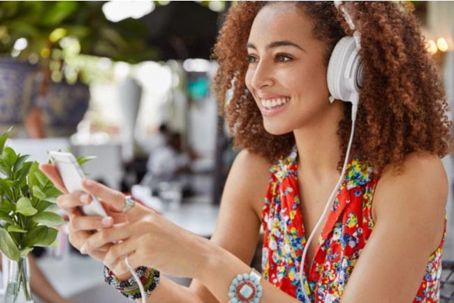 kvinna lyssnar på ljudbok och håller mobilen framför sig