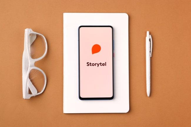 mobil med storytels logga ligger på block bredvid penna och solglasögon
