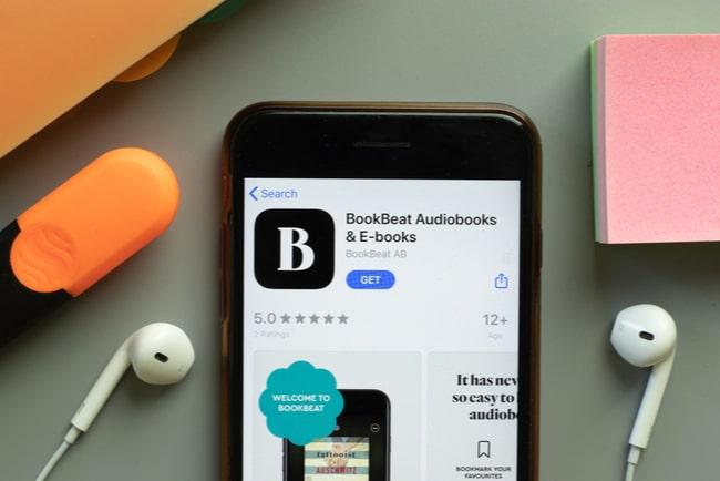 bookbeats app-logga på mobiltelefon som ligger på bord med hörlurar penna och block runtom