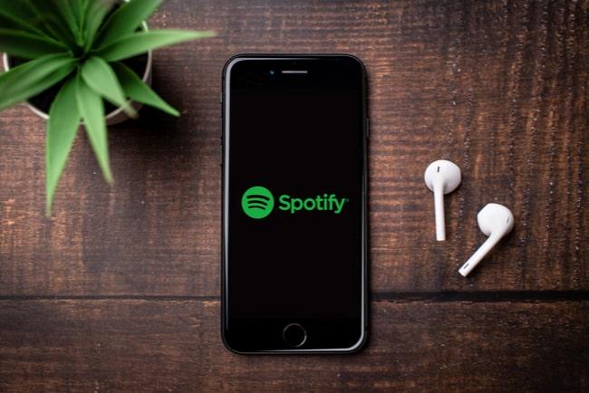 mobil med spotifys logga och vita hörlurar bredvid