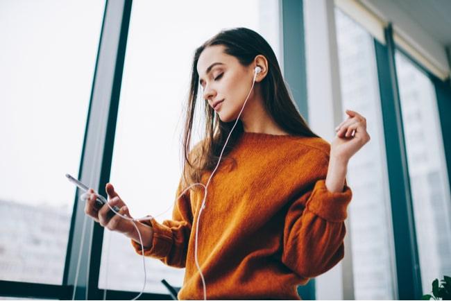 Ung kvinna står med mobil i handen och hörlurar i öronen.