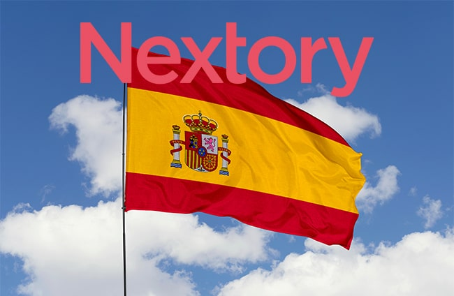 Spanska flaggan mot blå himmel och nextorys logga ovanför.