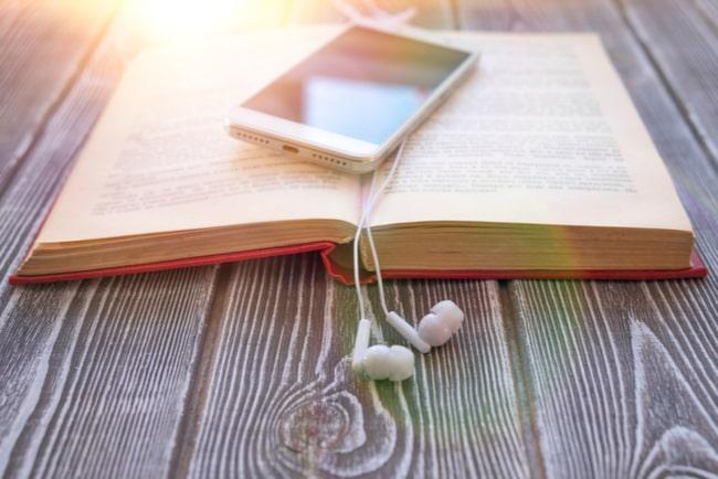 En bok ligger på ett träbord med en mobil och hörlurar på uppslaget.