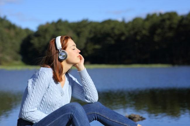 Kvinna med hörlurar sitter vid vattnet och blundar.