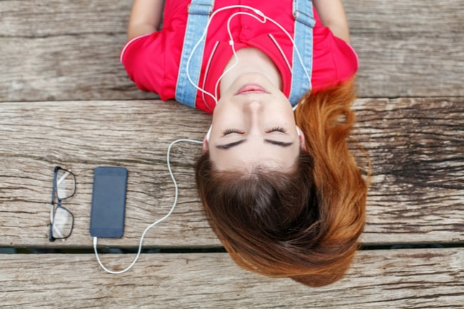 Tjej ligger på brygga med mobil bredvid sig och hörlurar i öronen.