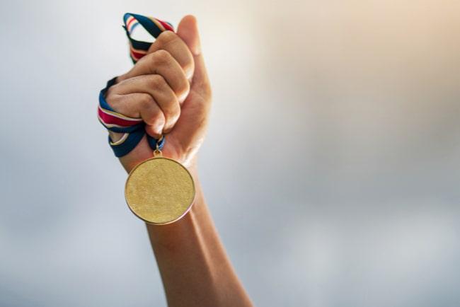 Hand håller upp guldmedalj mot blurrad bakgrund.
